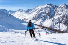 Sciatori che sciano in discesa nelle alte montagne e nel giorno soleggiato Fotografia Stock