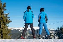 Sciatori della donna e dell'uomo sul paesaggio godente superiore della montagna immagine stock