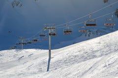 Sciatori di trasporto dell'ascensore di sci, snowboarders un giorno di inverno soleggiato luminoso Fotografie Stock