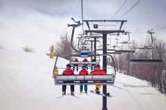 Sciatori e snowboarder su una seggiovia immagine stock libera da diritti