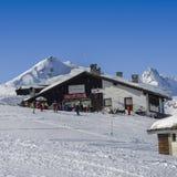 Sciatori e snowboarders accanto ad una cabina di legno nelle alpi italiane durante l'inverno, con lo spazio della copia Immagini Stock