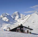 Sciatori e snowboarders accanto ad una cabina di legno nelle alpi italiane durante l'inverno, con lo spazio della copia Immagine Stock