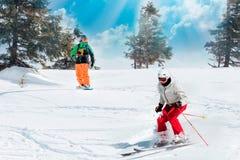 Sciatori e snowboarders che guidano su una stazione sciistica sulla montagna nevosa di inverno con la vista scenica del fondo del fotografia stock
