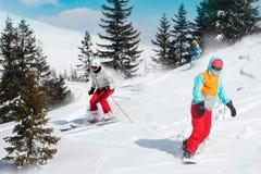 Sciatori e snowboarders che guidano su una stazione sciistica sulla montagna nevosa di inverno con la vista scenica del fondo del immagini stock libere da diritti