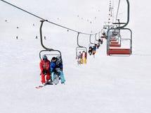 Sciatori e snowboarders sull'ascensore di sci contro il mountai nevoso di inverno Fotografia Stock Libera da Diritti