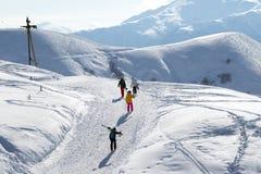 Sciatori e snowboarders sulla strada della neve alla mattina di inverno del sole Fotografie Stock