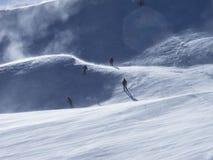 Sciatori in pista dello sci spazzata vento Immagini Stock