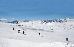 Sciatori sul pendio alpino del pattino Immagini Stock Libere da Diritti