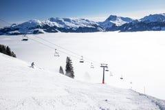 Sciatori sull'ascensore di sci che godono della vista alle alpi nebbiose in Austria ed il bello panorama nevoso del paese in mont Fotografia Stock Libera da Diritti