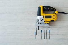 Scie à chantourner et exercices électriques sur une table en bois légère Photographie stock libre de droits