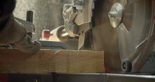 Scie à tronçonner tirée en gros plan découpant le bois dans de petites places à la fabrication banque de vidéos