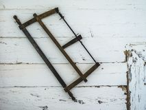 Scie accrochant sur le mur d'une vieille maison photo libre de droits