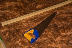 Scie avec la laine d'isolation thermique Photographie stock libre de droits