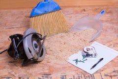 Scie tenue dans la main de circulaire avec la sciure et la casserole Images libres de droits
