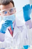 Science. Investigator checking test tubes. Man wears protective goggles Stock Photo