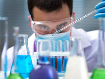 Science. Investigator checking test tubes. Man wears protective goggles Stock Photography