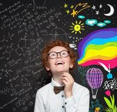 Science and arts occupations. Smiling smart boy kid on blackboard background with maths formula and art pattern.  stock photos