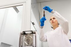 Woman with sulphuric acid in dropper at laboratory. Science, chemistry, industry and people concept - woman scientist or chemist with sulphuric acid in dropper stock photography