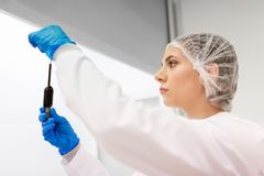 Woman with sulphuric acid in dropper at laboratory. Science, chemistry, industry and people concept - woman scientist or chemist with sulphuric acid in dropper royalty free stock images