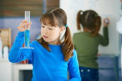 Science class at primary school. Elemantary age school girl looking at test tube in science class at primary school Stock Photography