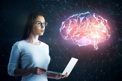 Science and communication concept. Side view of attractive european woman with laptop standing on blurry dark background with glowing digital brain. Science and Royalty Free Stock Photo