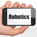Science concept: Hand Holding Smartphone with Robotics on display. Science concept: Hand Holding Smartphone with black text Robotics on display, 3D rendering Stock Image