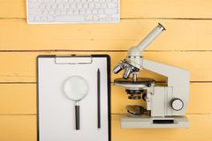 Science concept - microscope, magnifying glass, blank clipboard, computer keyboard on the yellow desk. Education and science concept - microscope, magnifying Royalty Free Stock Image