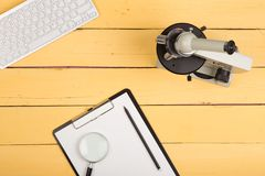 Science concept - microscope, magnifying glass, blank clipboard, computer keyboard on the yellow desk. Education and science concept - microscope, magnifying Royalty Free Stock Images