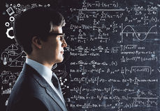 Science concept. Portrait of handsome businessman with business sketch and mathematical formulas on chalkboard in the background. Science concept stock images