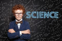 Science concept. Smart child boy on blackboard background with science formulas.  stock photography