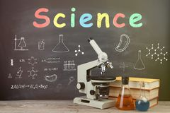 Education concept books on the desk in the auditorium. Science and education concept - books and microscope on the desk in the auditorium royalty free stock photo