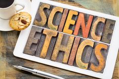 Science ethics word abstract on tablet. Science ethics word abstract in vintage letterpress wood type printing blocks on a digital tablet with a cup of coffee stock image
