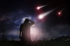 A science fiction edit of a man standing in a field as meteorites speed towards the earth at night with the stars in the sky.  stock images