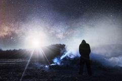 A science fiction night time edit. With a hooded figure looking at a bonfire and smoke with the sky full of stars and a bright lig. Ht in the sky royalty free stock image