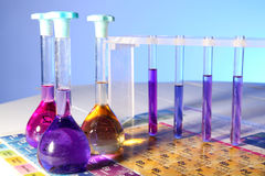 Science. Flasks and tubes full of chemicals standing on a periodic table royalty free stock image