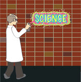Science graffiti. A scientist in a lab coat spray painting science on a brick wall Stock Photos