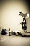 Science lab with chemical theme. Microscope on table for vintage science background Stock Image