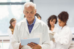 Science lecturer holding tablet pc in lab Royalty Free Stock Image