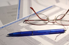 Science reports. With graphs on the table with blue pen and womans glasses royalty free stock photo