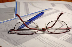 Science reports. With graphs on the table with blue pen and womans glasses Royalty Free Stock Photos