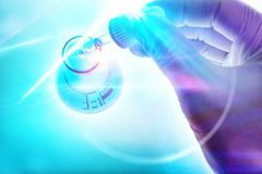 Hand of a scientist with dropper on blue background lights royalty free stock photography