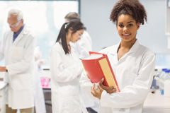 Science student holding large folder in lab. At the university Stock Images