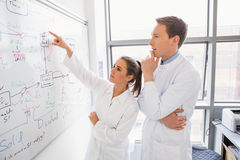 Science student and lecturer looking at whiteboard Royalty Free Stock Photography
