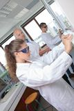Science student performing experiment wearing protective eyewear. Science Stock Images