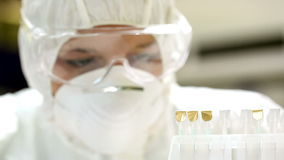Science student in protective suit comparing samples stock footage