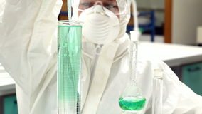 Science student in protective suit working with green chemicals stock video