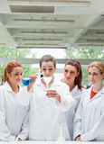 Science students pouring liquid in a flask. Portrait of science students pouring liquid in a flask in a laboratory Stock Photography