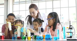 Science teacher and students, they do experiment. Science teacher and Asian students in science class, they do experiment, dyeing Chinese Cabbage by put it in stock video footage