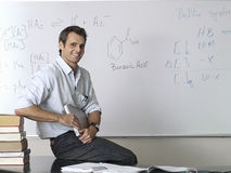 Science teacher sitting on desk beside whiteboard in classroom, smiling, portrait Stock Images