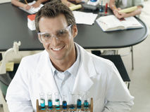Science teacher standing in classroom, holding rack of test tubes, smiling, portrait, elevated view Royalty Free Stock Images